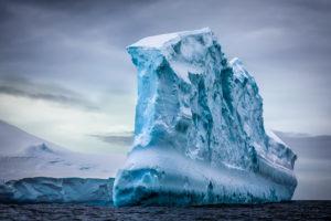 Antarctic iceberg in the snow floating in open ocean. Beauty world
